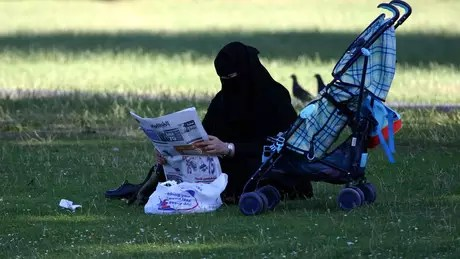De niqab, mulher lê jornal em parque em Londres