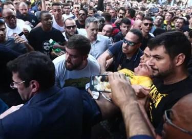 O candidato à Presidência da República pelo PSL, Jair Bolsonaro (de camiseta amarela), após ser esfaqueado durante ato de campanha em Juiz de Fora (MG), nesta quinta-feira, 06.