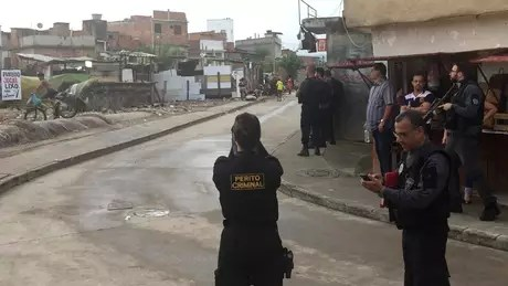 Peritos na rua São Daniel fotografando a torre branca ao fundo da comunidade