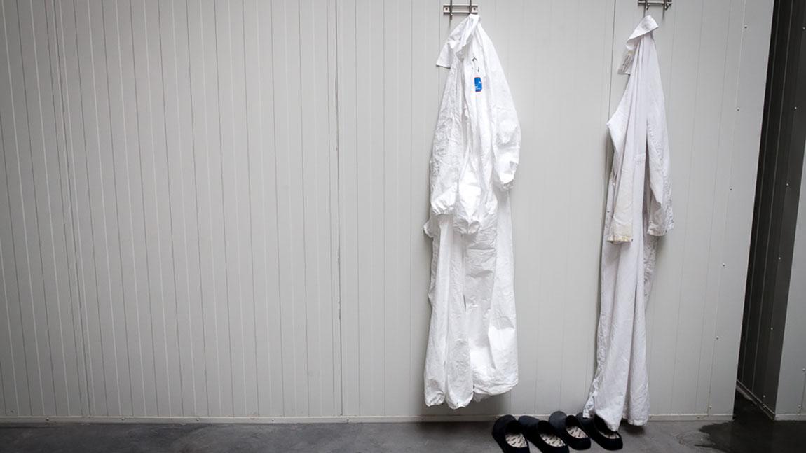 De hvite, kliniske arbiedsfrakkene henger på rekke ved inngangen til cannabislaboratoriet. (Foto: Matias Nordahl Carlsen)