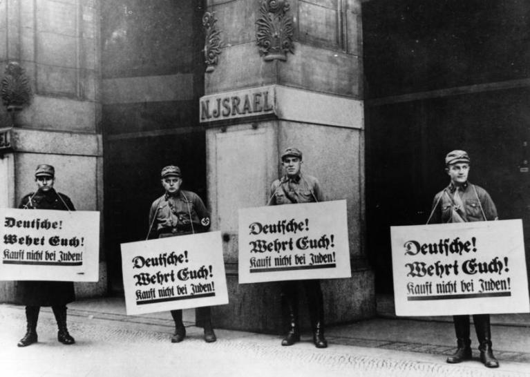 """Den anti-jødisk kampanjen pågikk i mange år. Dette bildet er fra april 1933, fem år før Krystallnatten. På bildet ser vi brunskjorter med plakater hvor det står """"Kamerater! Forsvar dere selv! Ikke kjøp fra jødene!"""" (Foto: General Photographic Agency/Getty Images)"""