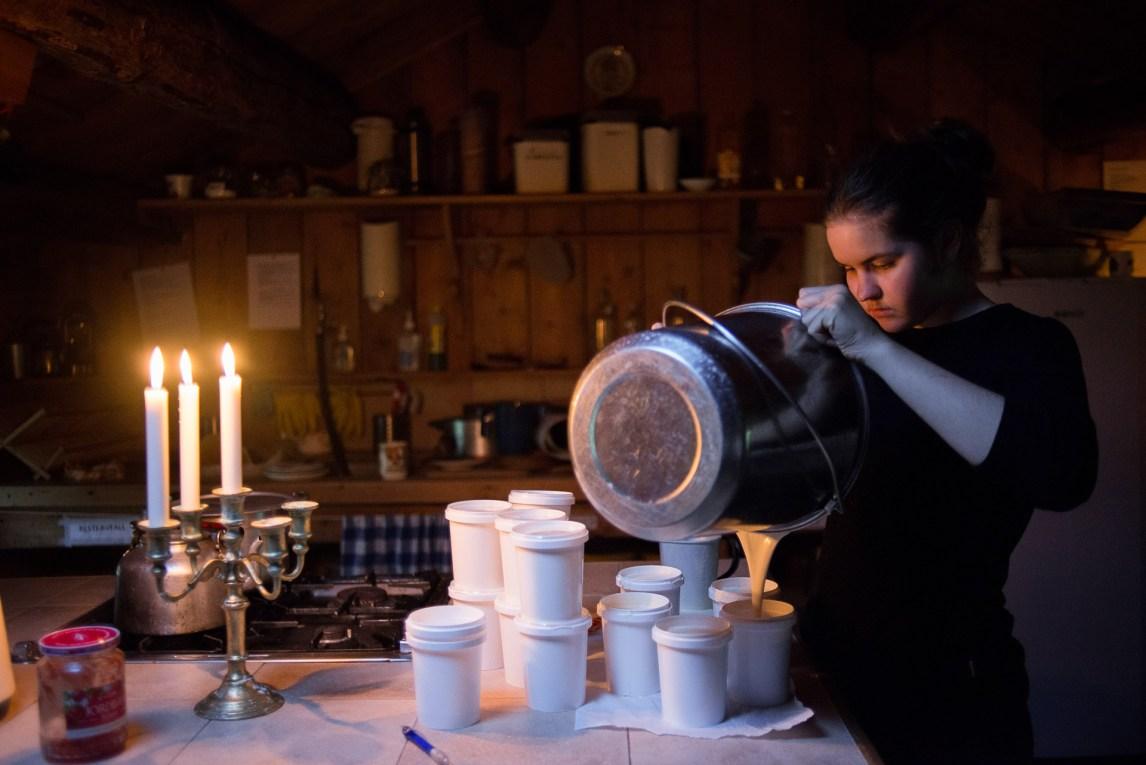 På setra lærer driverne flere måter å lage produkter ut av melk. Her heller Christine Beate Husøy (17) rømme i begre, som blir solgt til turistene som kommer innom. (Foto: Helle Gannestad)