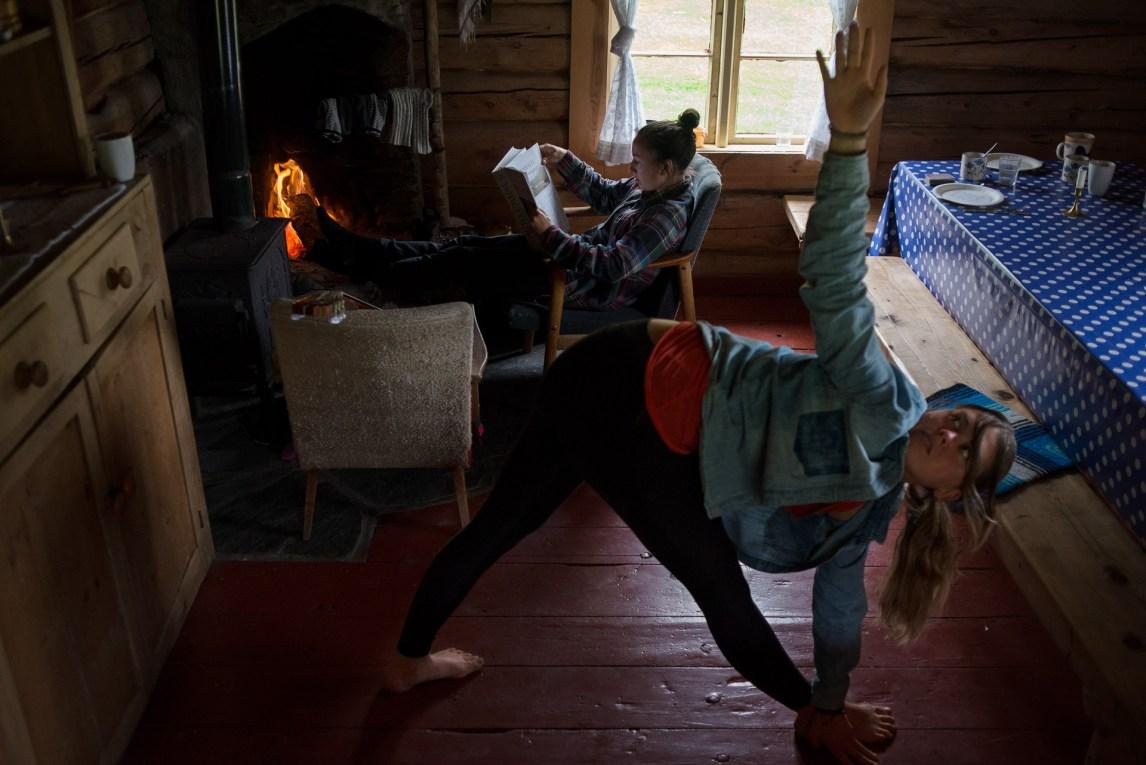 Camilla Vanessa Askeland (23) fra Sandnes gjør yoga for å løse opp i kroppen. Arbeidet på setra er fysisk hardt, fra morgen til kveld. I bakgrunnen leser Guro Stenhammer Aanerød (23) fra Elverum en bok. (Foto: Helle Gannestad)