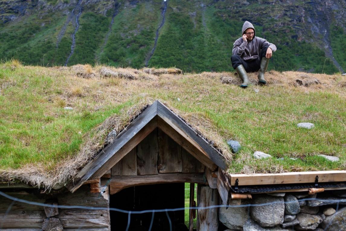 Det er ikke mange steder med dekning på setra, men på taket på det gamle fjøset får en nok til å ringe ut. Etter en ukes opphold tar Markus Giske (22) seg tid til en telefonsamtale. (Foto: Wanda Nathalie Nordstrøm)