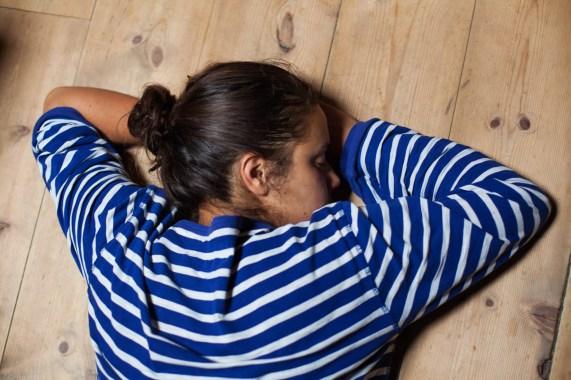 Det er lange dager på setra, Aisha Marie Heim (23) tar et minutts hvil på gulvet. Foto: Wanda Nathalie Nordstrøm
