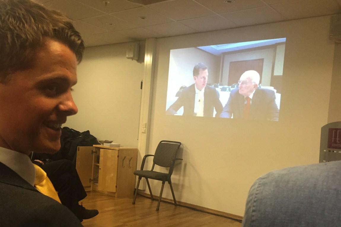 Simens forbilde og pengecoach, JT Foxx dukker opp på skjermen i salen. Det presenteres som en direkteoverføring, men det er tydelig et opptak. (Foto: Webjørn S. Espeland, NRK)