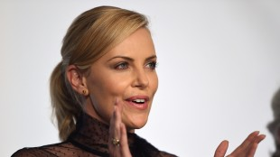 Charlize Theron applauderer under pressekonferansen for Mad Max: Fury Road i Cannes (Foto: AFP PHOTO / ANNE-CHRISTINE POUJOULAT).