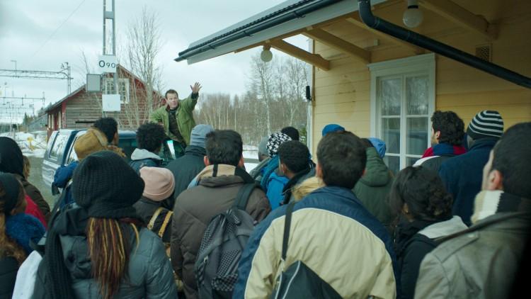 Per Primus (Anders Baasmo Christiansen) tar i mot asylsøkerne på togstasjonen i Welcome to Norway! (Foto: Motlys / Norsk Filmdistribusjon).