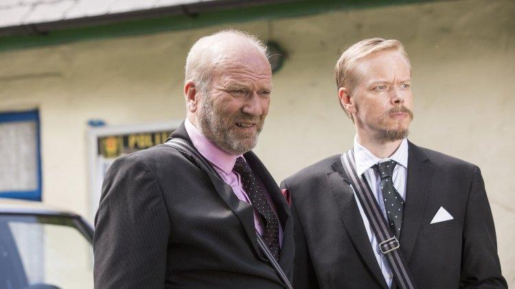 Ingar Helge Gimle og Joachim Rafaelsen er knallgode som de to skurkete byråkratene fra henholdsvis turistvesenet og vegvesenet. (Foto: Sharing og Cinenord Kidstory)