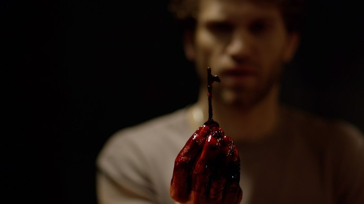 En blodig hånd som holder en nøkkel