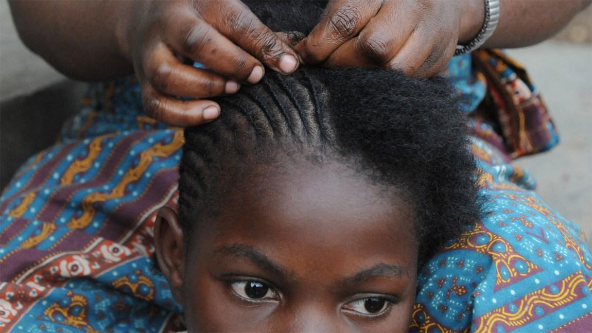 Jente blir flettet på tradisjonelt afrikansk vis. Kjent som frisyren corn rows. (Foto: Roberto Schmidt, Scanpix/AFP)