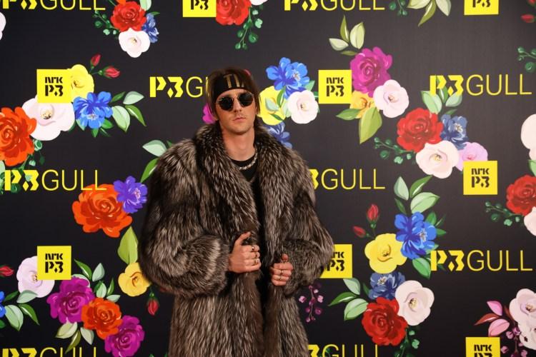 Andreas «Tix» Haukeland er ikledd en stor pelskåpe, solbriller, pannebånd, og har mange gullkjeder på. Han står foran en P3 Gull-pressevegg.