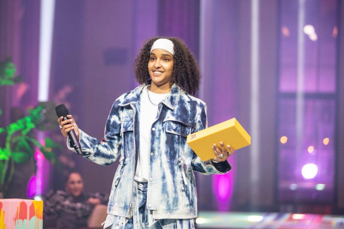 Musti står på scenen med mikrofon i den ene hånden og prisen i den andre.