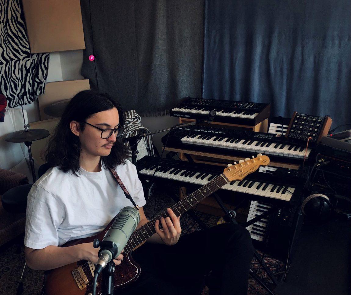 Noah sitter og klimprer på en guitar i studi. Han har halvlangt brunt hår som når han til skuldrene, store svarte briller, bart og en hvit t-skjorte på. Bak han står et stort orgel.