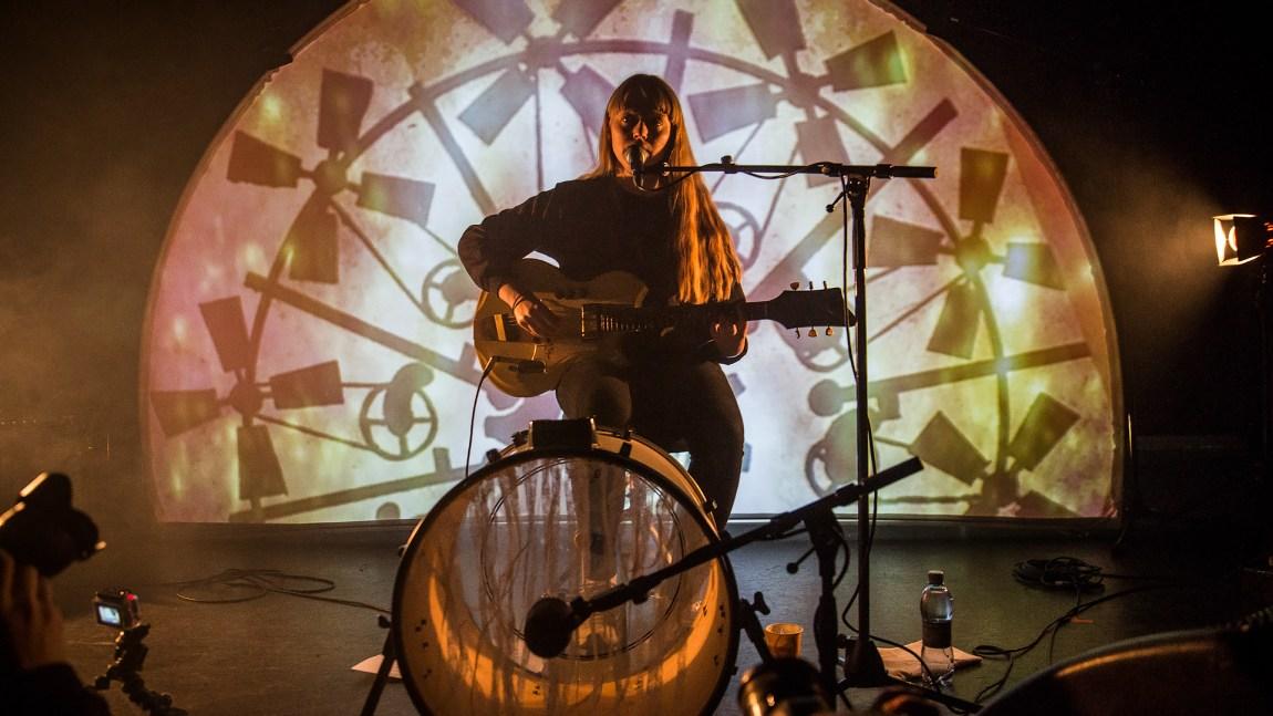 Et bilde av Vilde Tuv live alene på scenen med kun gitar, mikrofon og trommer