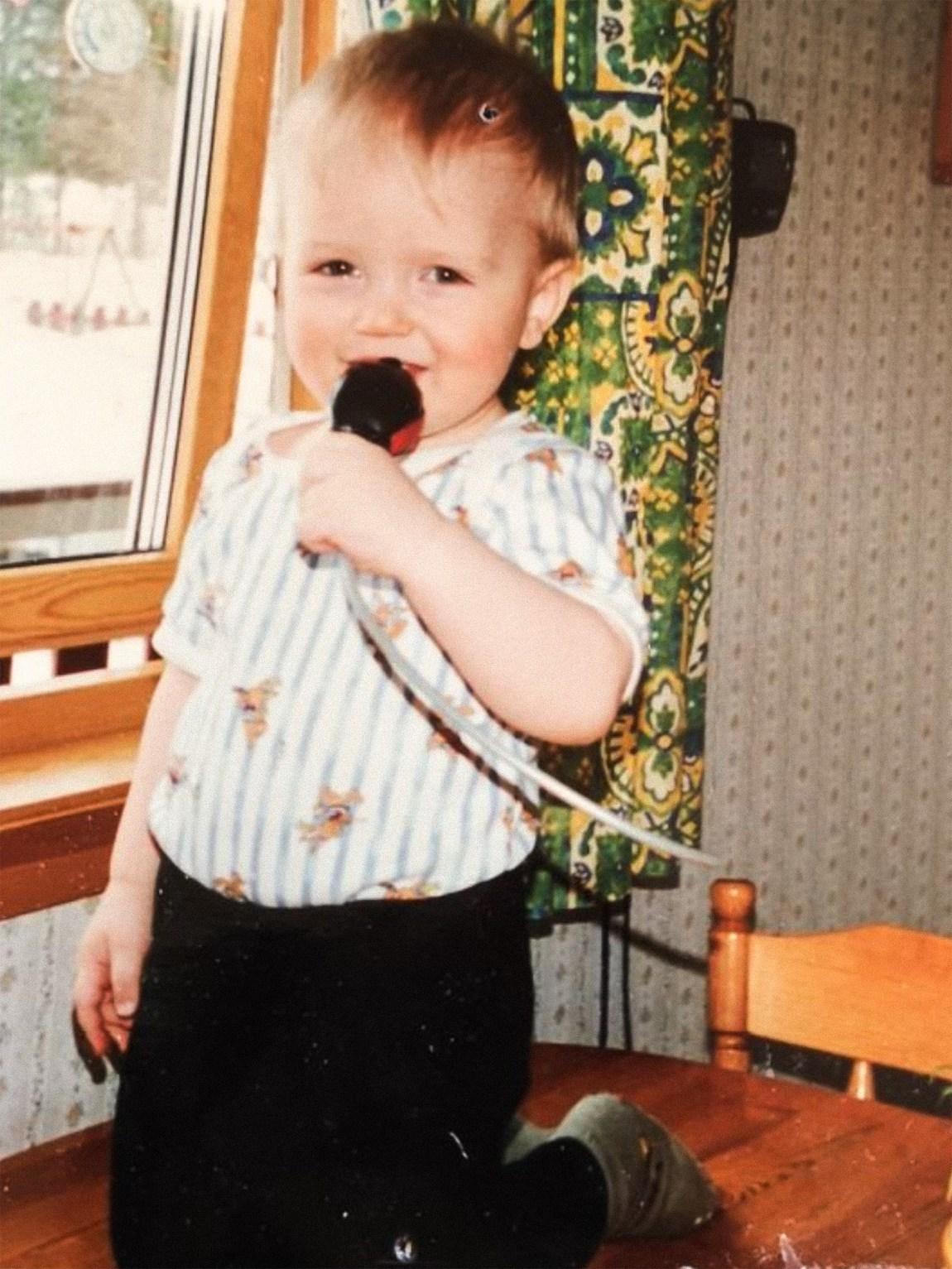 Et bilde av Simon som lite barn. Han er på toppen av det som ser ut som et kjøkkenbord, med en mikrofon i hånda
