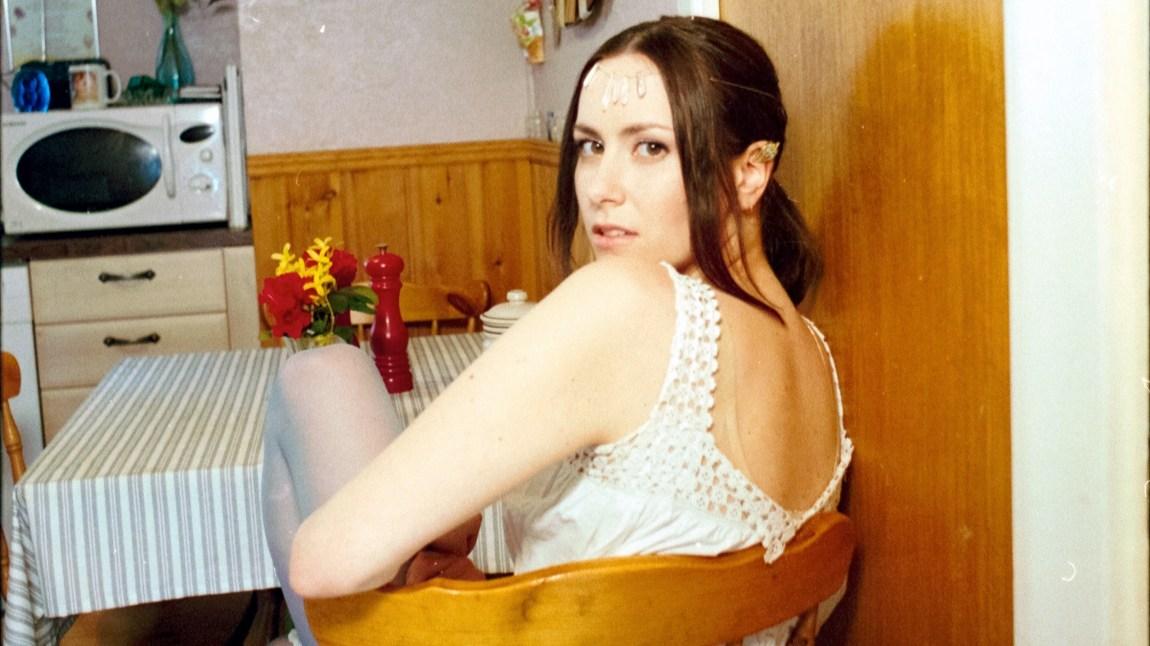 Iris sit ved eit lite kjøkkenbord, med ryggen mot kamera, og ser seg over skuldra.