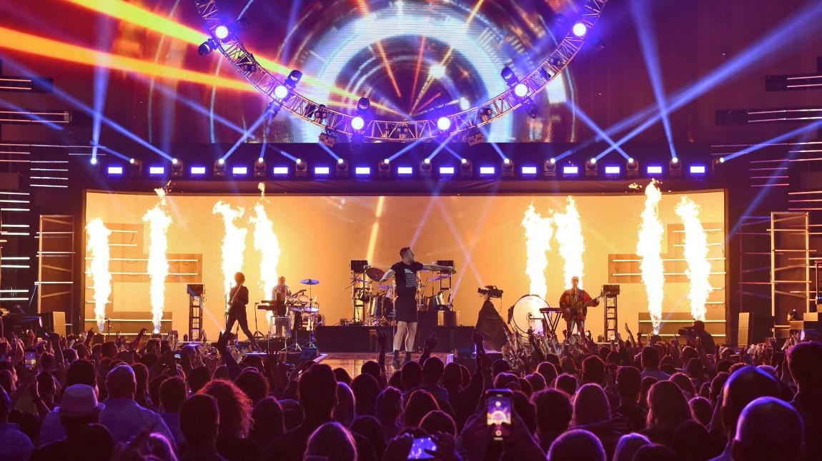 Imagine Dragons på scena, med lysshow og pyroeffektar.