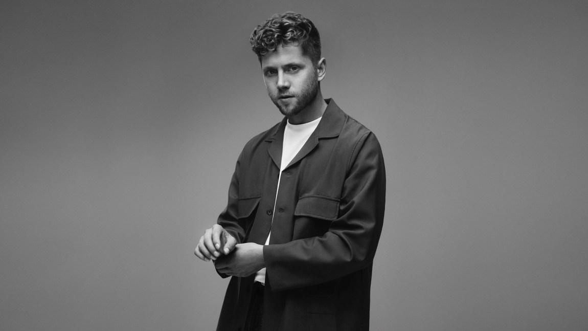 Svart/hvitt-foto av Daniel Kvammen som justerer jakkeermet