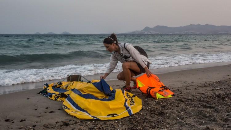 Silje Ese sjekker en ødelagt gummibåt på stranda i Kos. (Foto: Foto: Marius Arnesen, NRK).