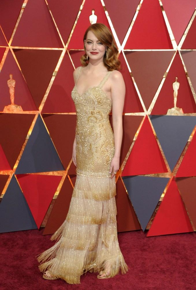 Oscar-nominerte Emma Stone strålte i en av kveldens trendfarger, gull. Kjolen er  fra Givenchy. Foto: AP/