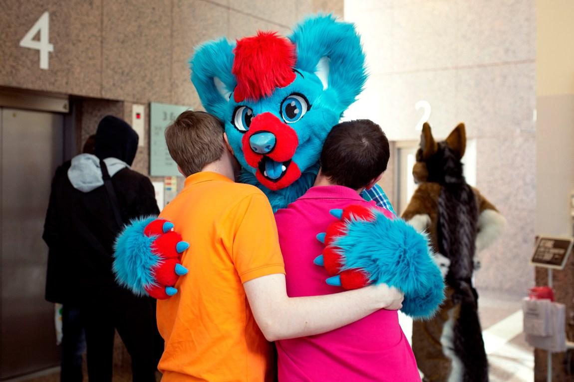 En fargesprakende bamse holder rundt to unge menn.