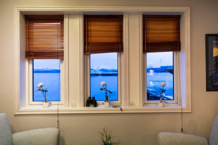 Tre vinduer på en hvitgrå vegg med utsikt mot havet og Hurtigruta. I hver vinduskarm står en hvit rose, og ute er det blåtime.
