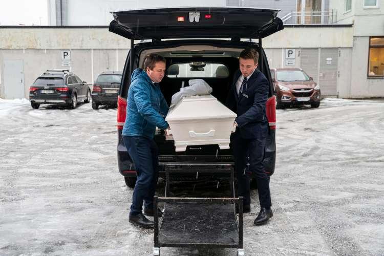 Faren til kristian og Kristian bærer ut en kiste fra bagasjerommet. Far til venstre er ikledd lyseblå jakke, sønn til høyre,  iført mørkelbå dress. På bakken er det lett snø og bak dem en parkeringsplass med biler.