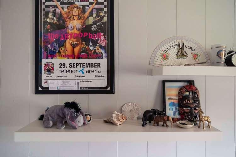 Hvit vegg med hvite hyller på Sondres rom. Til venstre henger en plakat av Lady Gaga hvor hun hever armene i været og smiler. Det er en reklameplakat for konserten hennes. På hylla under ligger en Tussi-bamse, strandskjell, treelefanter og en afrikansk maske. På hylla over ligger en håndvifte, et krus og en gammeldags vekkerklokke.