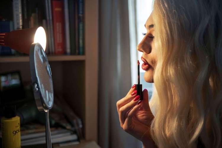 Til høyre på bildet ser Sondre seg i sminkespeilet og holder en lipgloss med høyre hånd, og påfører den. Neglene er dekket av rød neglelakk. Til venstre står sminkespeilet.