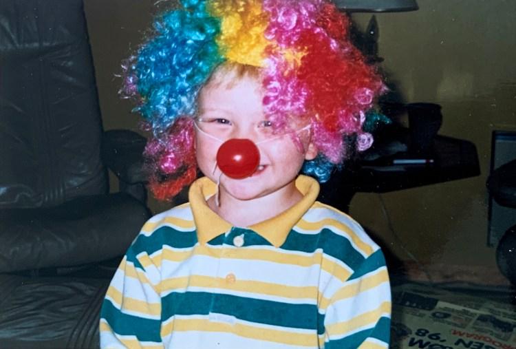 Barndomsbilde tatt med analogt kamera. Nærportrett av Sondre, med kloveparykk i rosa, gult, rødt og blått, med en rund, rød klovnenese på nesa. Han smiler.