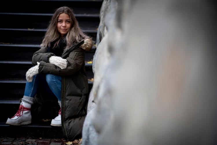 Natalie sitter til venstre i bildet på en steintrapp. Hun ser rett i kamera, med et lurt smil. Det lange brune håret er utslått, og hun er godt kledd for en kald høstdag i Umeå.