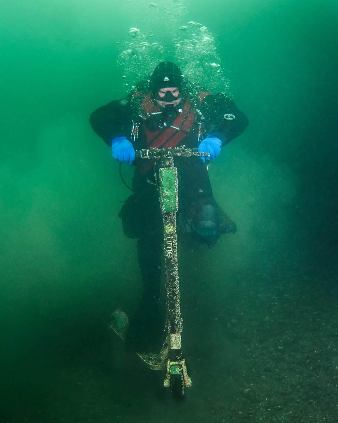 Bildet viser ein dykkar som later som om han kjører på ein elsparkesykkel under vatn.