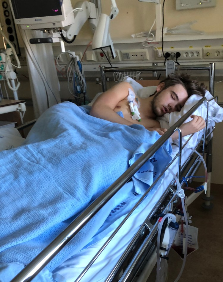 Marcus ligg i ei sjukehusseng og søv. Overkroppen er naken, og viser fleire slangar og elektrodar som er festa på brystet hans.