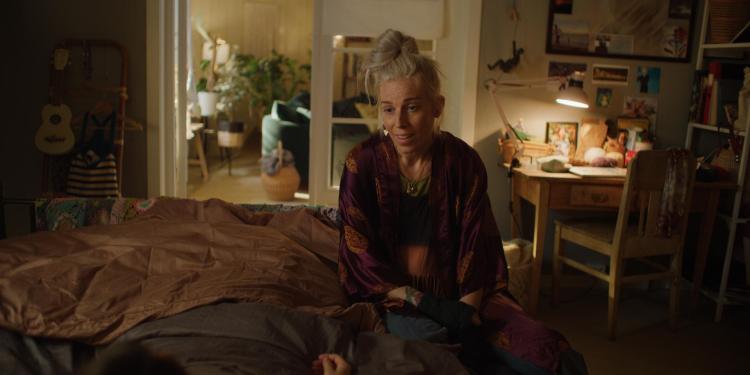 Gabrielle sitter i senga under innspillingen av serien.