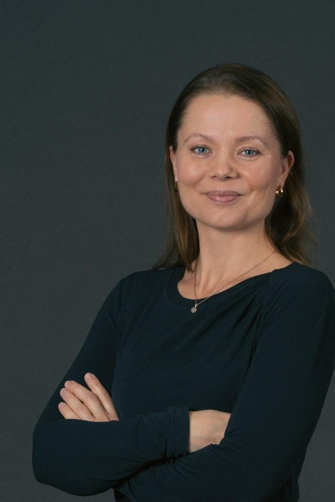 Portrettbilde av Kristina Moberg som har armane i kors, og som smiler til kamera.