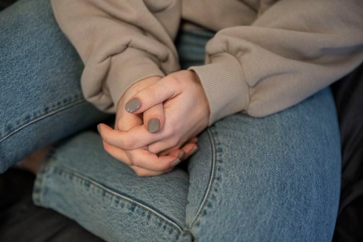Nærbilde av at Synne folder hendene. Hendene er knyttet, og ligger i fanget. Synne har på en bage-grå neglakk som matcher hettegenseren. Buksa er lysblå.