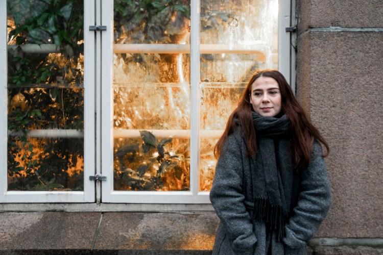Synne står lent mot en murvegg og en hvit vinduskarm. Hun har på grå kåpe og skjerf, og ser ut mot venstre med hendene i lomma. Gjennom vinduet bak henne skimtes grønne planter og et oransje plantelys.