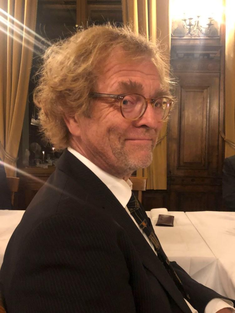Bilde av forsker Svein Mossige som har på en sort dress mens han stilt litt på sida. Han har på briller og ser inn i kamera.