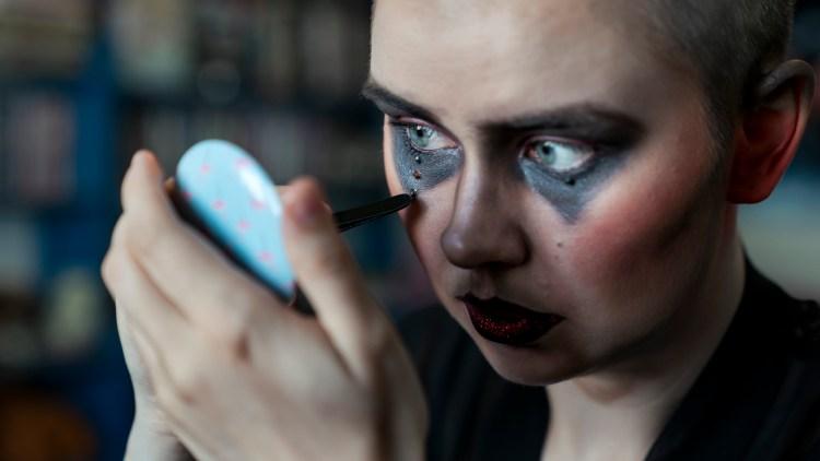 Nærbilde av Åshild som sminker seg. Hun har malt sorte trekanter under øynene og limt på tre paljetter under høyre øye. Hun ser inn i et håndspeil mens en sminkekost strykes nedover kinnet.