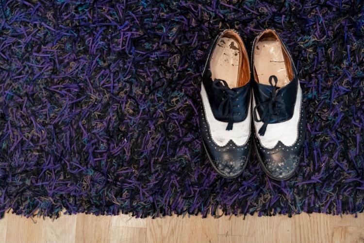 På bildet står et par gammeldagse lakksko på et lilla og sort teppe. Skoene er hvite og sorte og skinnet inni er slitt.