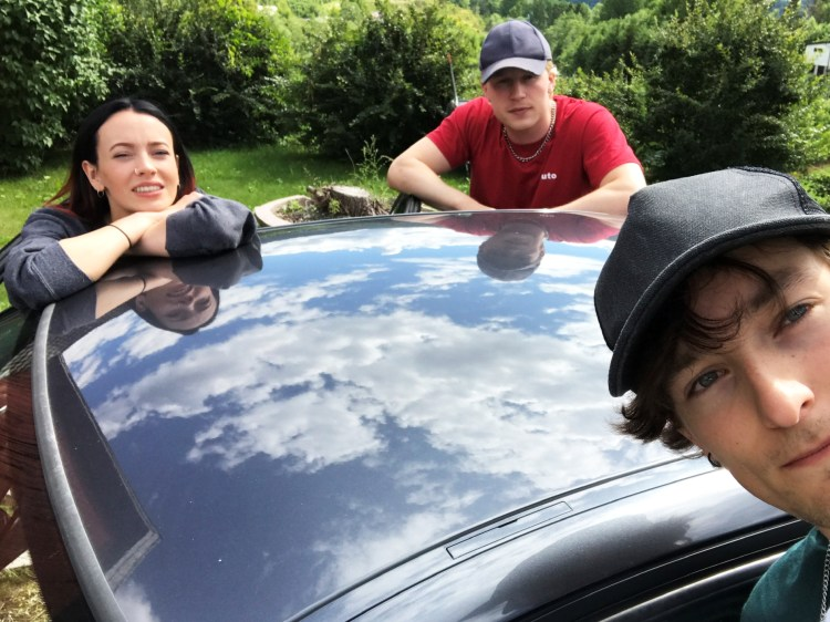 Sjur Vatne Brean, i bilde plassert i høyre hjørne, har tatt en selfie på filmsettet. Her står han på en side av bilen, med Maja Christiansen og Odin Waage på andre. Alle tre er lent over bilen, som vi kun ser taket på. De stirrer alle mot kameraet.