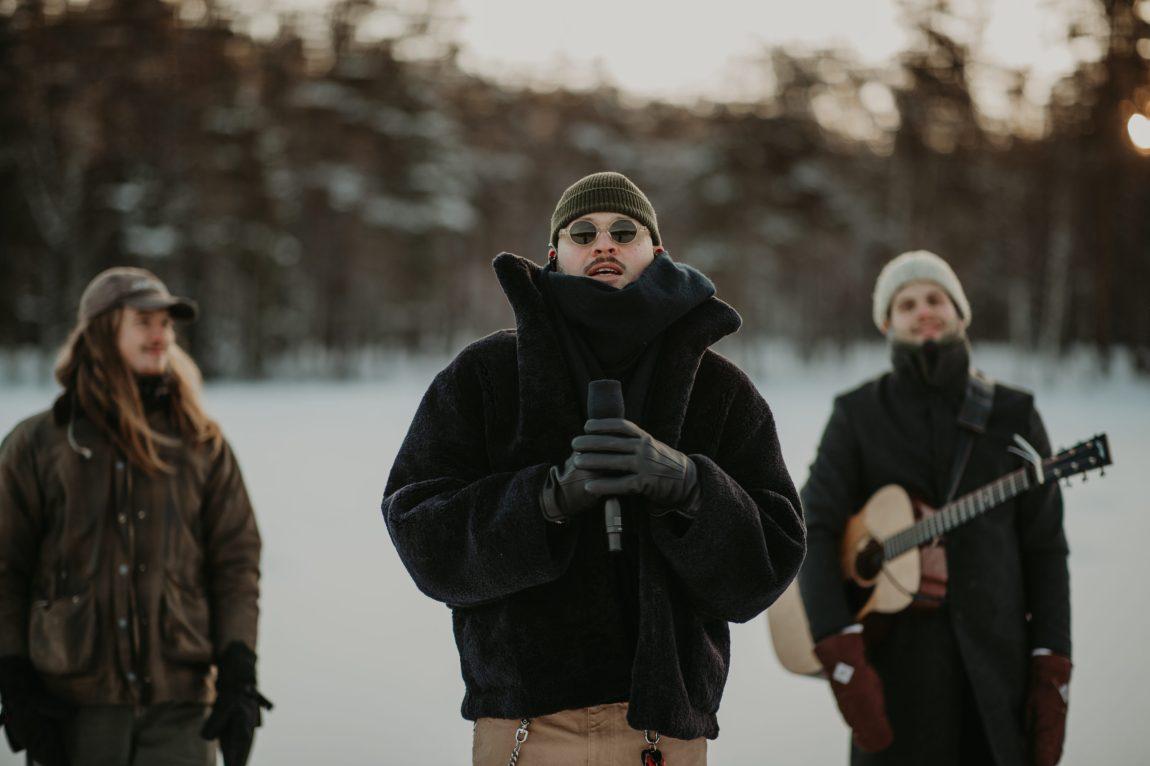 Stig Brenner står med mikrofonen i hånda med gitarist og trommis på hver sin side. De står på et snøkledd, islagt vann inne i marka med skogen bak seg.