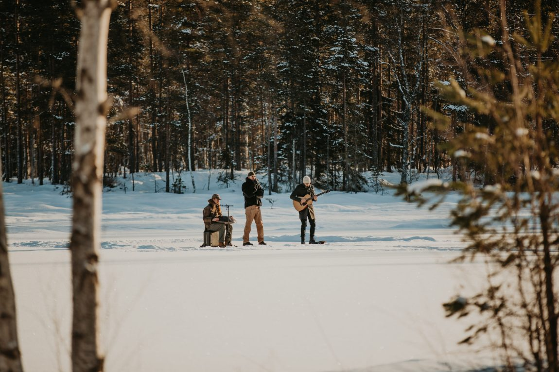 Stig Brenner står sammen med trommis og gitarist på et iskledd vann midt ute i marka. De tre ser små ut der de står langt unna fotografen foran snøkledde trær.
