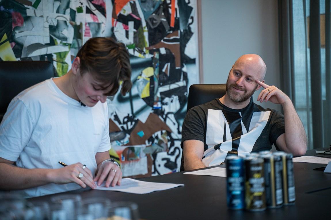 På dette bildet sitter Emil, verdensmester i Fortnite, med papir og penn i hendene. Han skal skrive kontrakt med Nordavind. Stein Willmann, daglig leder i Nordavind, sitter ved siden av og ser på Emil mens han smiler.