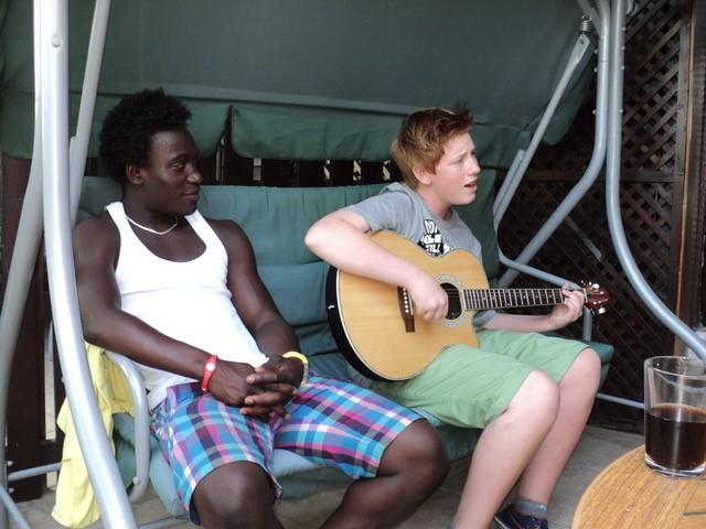 Cidi sitter i en gyngende benk ved siden av Bjarte som spiller på gitaren og synger. De har begge shorts og korterma trøyer på, det er sommer. Cidi sitter med hendene i fanget, mens Bjarte har gitaren i fanget som han spiller på.