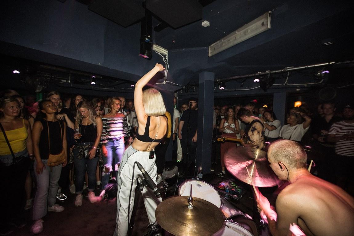 Helene står med ryggen til og synger til publikum. Hun har armen i været og lener seg bak. Rett bak henne ser vi Johan som spiller trommer og ved siden av henne står gitaristen. Publikummet er samlet tett rundt de.