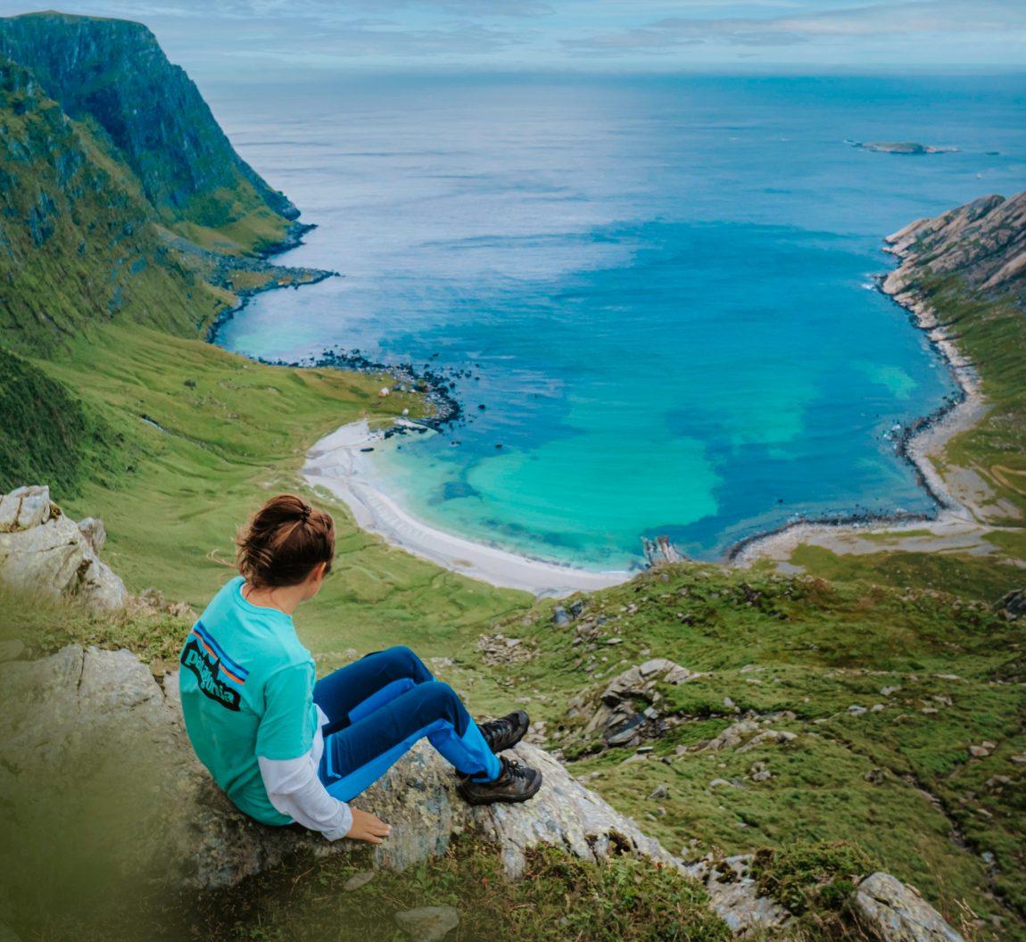 Oppe i fjellhugget, rett over en strand med turkist og lyseblått vann, sitter Helene og stirrer utover horisonten. Hun er helt alene i bildet som strekker seg i flere kilometer, både på land og til havs. Dette er et melankolsk og vakkert landskapsfoto av et isolert kjær – Vetvika.