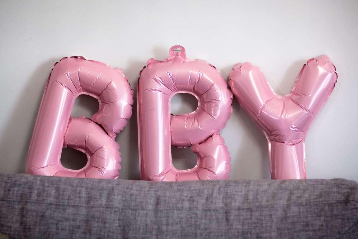 Tre ballongbokstaver i rosa staver hviler på sofaryggen. De staver BBY.