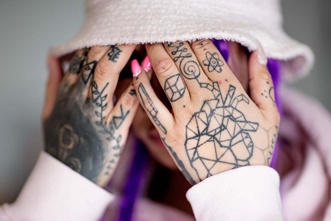 Nærbilde av at Helene holder hendene foran ansiktet. Hendene er tett tatovert.